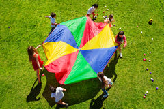 Kids going round in a circle with bright parachute. Top view picture of seven kids going round in a circle on the green lawn and holding rainbow parachute Stock Photos