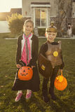 Kids Going Trick or Treating on Halloween. Two cute kids in Halloween costumes going trick or treating. Photo shot at early evening on Halloween night Royalty Free Stock Image