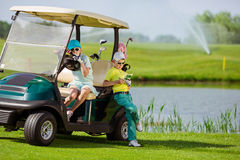 Kids on golf. Boy and girl resting near golf car at golf course at summer day Royalty Free Stock Photos