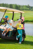 Kids on golf. Boy and girl resting near golf car at golf course at summer day Stock Image