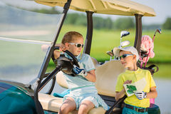 Kids on golf. Boy and girl resting near golf car at golf course at summer day Stock Photos