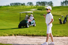 Kids golf competition. Boy playing golf and hitting from bunker Stock Photography