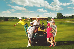 Kids golf competition. Children posing near golf car at golf course at summer day Stock Photos