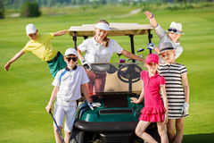 Kids golf competition. Children posing near golf car at golf course at summer day Royalty Free Stock Photos