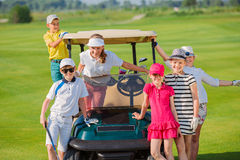 Kids golf competition. Children posing near golf car at golf course at summer day Stock Photo