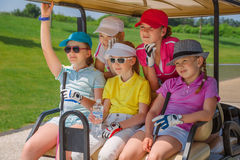 Kids golf competition. Girls walking in golf car at golf course at summer day Royalty Free Stock Photos
