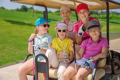 Kids golf competition. Girls walking in golf car at golf course at summer day Stock Photography