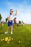 Kids golf school. Happy boy golf player practicing in golf school Royalty Free Stock Images