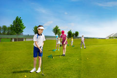 Kids golf school. Happy boy golf player practicing in golf school Stock Photos