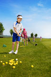 Kids golf school. Happy boy golf player practicing in golf school Stock Images
