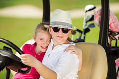 Kids on golf. Two girls walking in golf car at golf course at summer day Stock Images