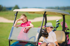 Kids on golf. Two girls walking in golf car at golf course at summer day Stock Photography