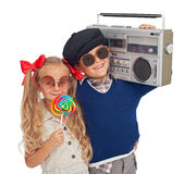 Kids gone retro. Happy kids gone retro - holding casette player and large lollipop Stock Photo