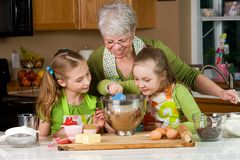 Kids and Grandma Baking in the kitchen. A Grandma teaching her Grandchildren how to bake royalty free stock image