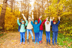 Kids group with arms up standing in row together Stock Photo