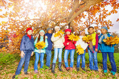 Kids group with bunches of yellow maple leaves Royalty Free Stock Images