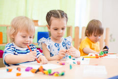Kids group doing arts and crafts in day care centre Stock Photos