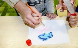 Kids group making arts and crafts in kindergarten. Children spending time in day care centre with the great interest. Children spending time in day care centre royalty free stock photography