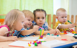 Kids group making arts and crafts in kindergarten. Children spending time in day care centre with the great interest. Kids group making arts and crafts in royalty free stock images
