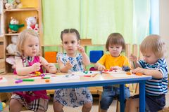 Kids group making arts and crafts in kindergarten. Kids group making arts and crafts in kindergarten or daycare center royalty free stock photography