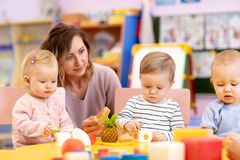 Kids group playing with teacher in day care centre playroom royalty free stock image