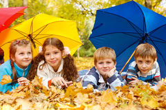Kids group under umbrellas. Kids group hiding under colorful umbrellas Stock Photo