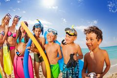 Kids group vacation portrait on a beach. Happy boys and girls in swim suits standing on the beach on hot summer vacation day wearing scuba masks holding swimming Stock Photos