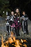 Kids In Halloween costumes Cooking Marshmallows On Campfire Royalty Free Stock Photography