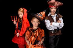 Kids in halloween costumes. Of devil, witch and pirate posing isolated on black royalty free stock photography
