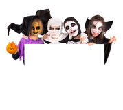 Kids in Halloween costumes. Kids with face-paint and Halloween costumes over a white board Stock Images