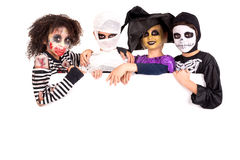 Kids in Halloween costumes. Kids with face-paint and Halloween costumes over a white board Stock Image