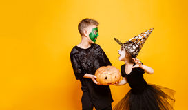 Kids in Halloween Costumes Playing with Pumpkin Stock Photo