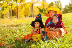 Kids in Halloween costumes sitting on the grass Royalty Free Stock Photo
