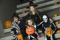 Kids In Halloween Costumes Sitting On Stairs Royalty Free Stock Images