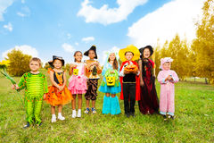 Kids with Halloween costumes stand in row. Children in different beautiful Halloween costumes stand in row together in the field stock photos