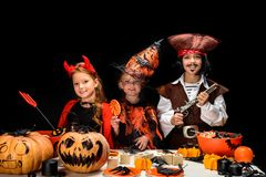 Kids in halloween costumes with sweets. Kids in halloween costumes of devil, witch and pirate with jack o lanterns and sweets, isolated on black stock photos