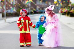 Kids on Halloween trick or treat. Children in Halloween costumes with candy bags walking in decorated city neighborhood trick or treating. Baby and preschooler royalty free stock photos