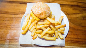 Kids Hamburger Meal With French Fries. A kids hamburger meal. The burger has a plain grilled beef with cheddar cheese and BBQ sauce Stock Photo