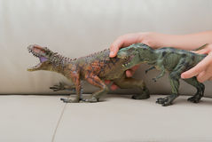 Kids hand catching a brown Carcharodontosaurus and a green tyrannosaurus toy Royalty Free Stock Images