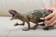 Kids hand catching a brown Carcharodontosaurus and a green tyrannosaurus toy Royalty Free Stock Photo