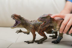 Kids hand catching a brown Carcharodontosaurus and a green tyrannosaurus toy Stock Images