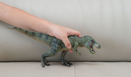 Kids hand catching a green tyrannosaurus toy on a sofa Stock Images