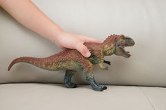 Kids hand catching a tyrannosaurus toy on a sofa. At home Stock Images