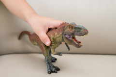 Kids hand catching a tyrannosaurus toy on a sofa Royalty Free Stock Photos