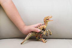 Kids hand catching a velociraptor toy on a sofa Royalty Free Stock Photo