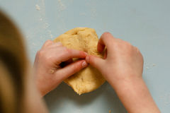 Kids hand with cookies cutter on cookies dough Stock Image