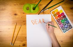 Kids hand drawing a greeting on blank page, top view stock image