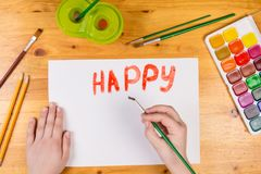 Kids hand drawing a greeting card with paintbrush at the table stock image