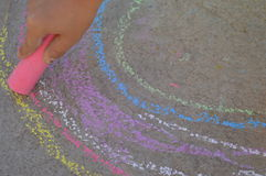 Kids hand drawing with a pink chalk on the street. Kids hand drawing a rainwob with a pink chalk on the street Stock Images