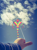 Kids hand holding a flying kite Stock Photos